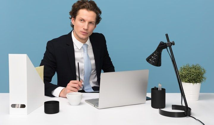 man-sitting-with-laptop-computer-on-desk-and-lamp-1586996